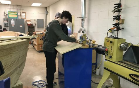 Senior Dylan Barrett works in the woodshop to cut holes for the newspaper stand project the club has taken on.
